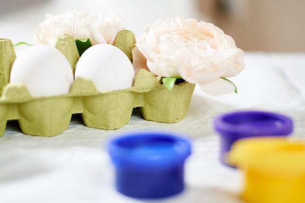 明るい春の休日の活動をペイントでイースターの卵を塗る Premium写真