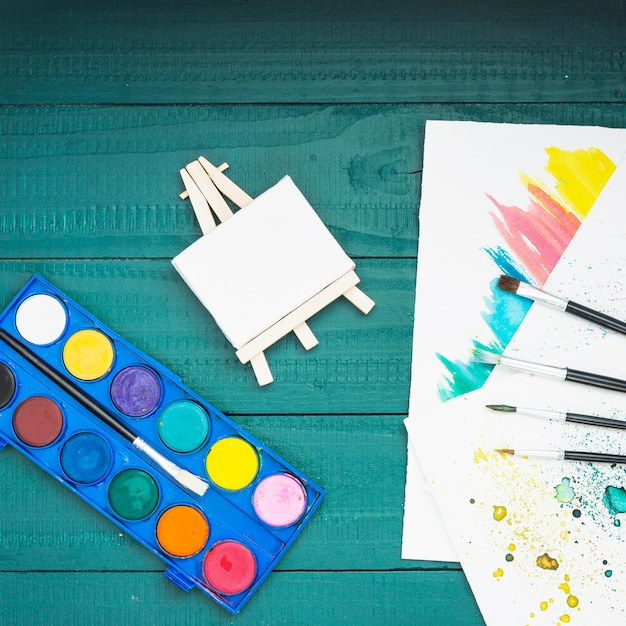 Painting equipment and hand drawn sheet over painted wooden table Free Photo