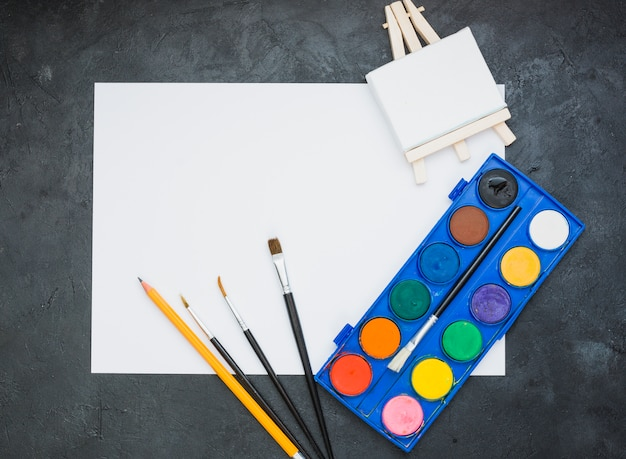 Painting equipment and white drawing paper with miniature wooden easel Free Photo