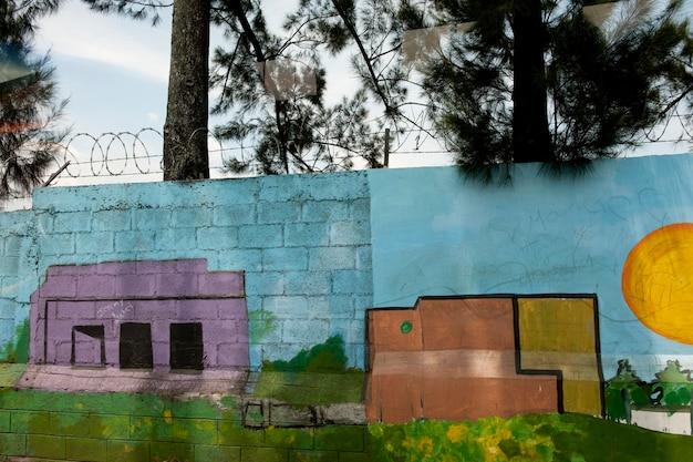 Окраска домов и зданий на бетонной стене из шлакобетона, с колючей проволокой Premium Фотографии