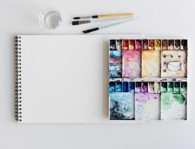 Painting palette sketchbook paper brushes white table Photo