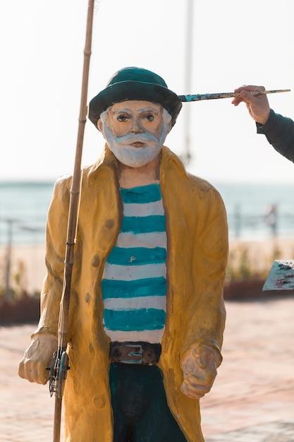 昔の漁師の彫刻を描いています。 無料写真