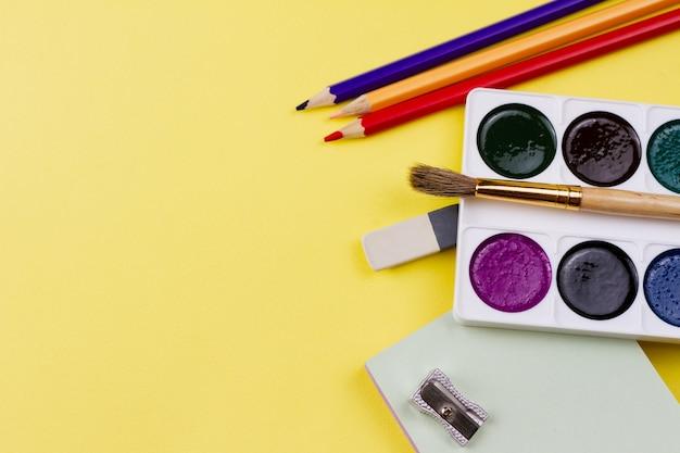Принадлежности для рисования на желтом фоне. Premium Фотографии