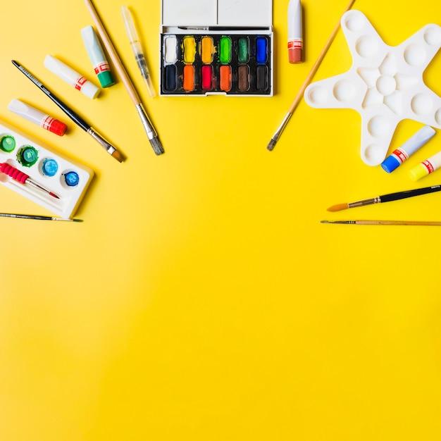 Paintingsupplies on yellow background Free Photo