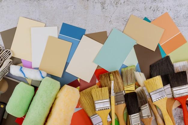 Инструменты рисования различными кистями, валиком и выбором цветовой палитры на деревянном столе Premium Фотографии