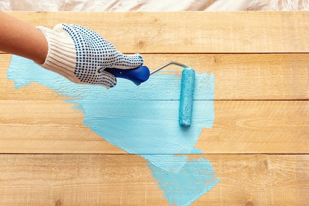 Painting with the paint roller blue color paint on the wooden Premium Photo