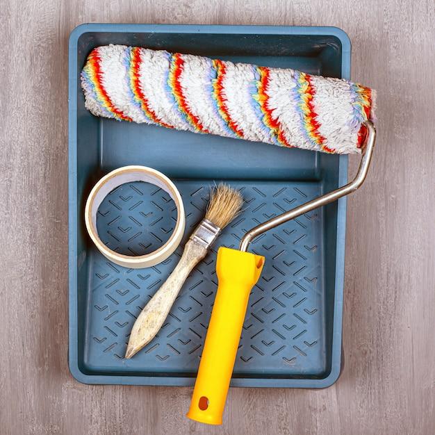 Концепция малярных работ. набор инструментов для покраски и ремонта стен. валик и кисть. Premium Фотографии