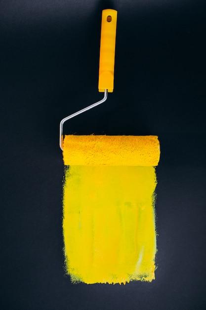 黄色の塗料で黒の背景に分離された修理用paintroller 無料写真