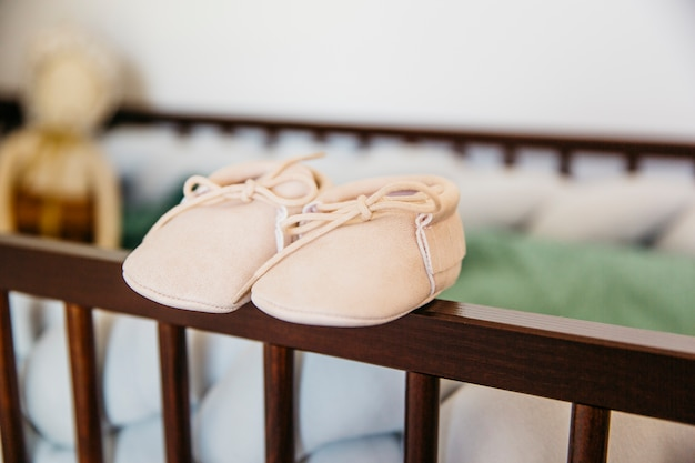Pair of baby shoes on the edge of wooden crib Free Photo