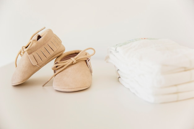 Pair of baby shoes and stacked of diaper on beige background Free Photo