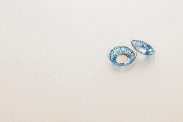Pair of blue contact lenses on gray  background Free Photo