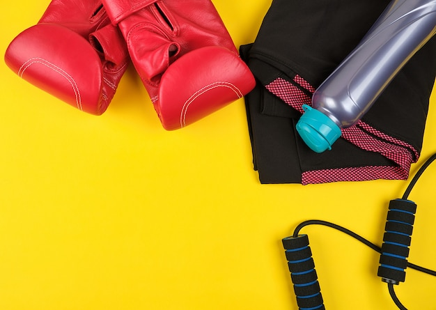 Pair of blue sneakers, red leather boxing gloves and black jump rope Premium Photo