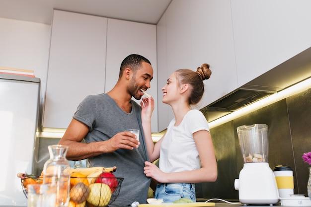 Coppia flirtare in cucina e mostrare il proprio amore. la moglie dà al marito di provare un frutto, tiene la sua maglietta. coppia con passione e felicità che si guardano l'un l'altro. appassionati di una dieta sana. Foto Gratuite