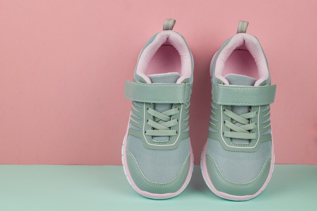 A pair of grey fashionable sneakers on blue and pink Premium Photo