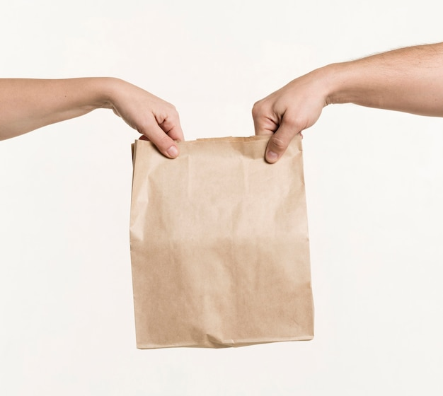 Pair of hands holding paper bag Free Photo