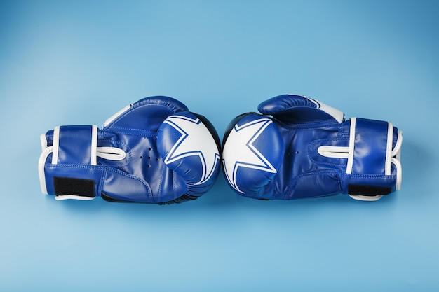 A pair of leather boxing gloves on a blue background, free space Premium Photo