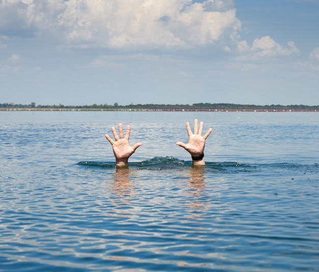 Pair of masculine hands sticks out of the sea water on a summer day Premium Photo