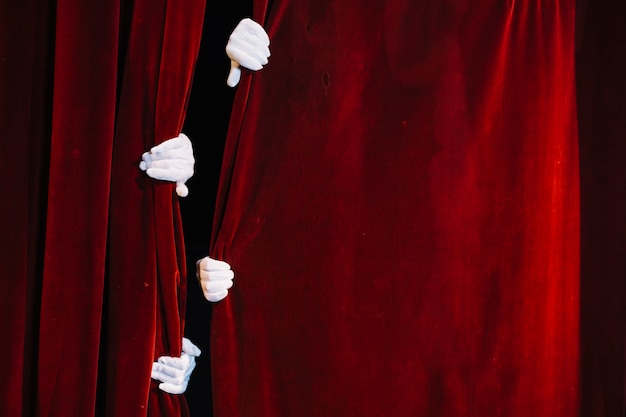 Pair of mime's hand holding closed red curtain Free Photo