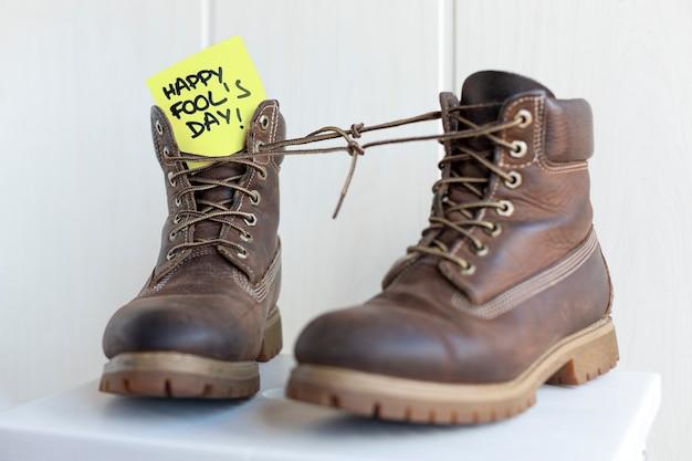Happy fool'sdayというフレーズのメモと一緒に結ばれた靴ひも付きのブーツのペア。 Premium写真