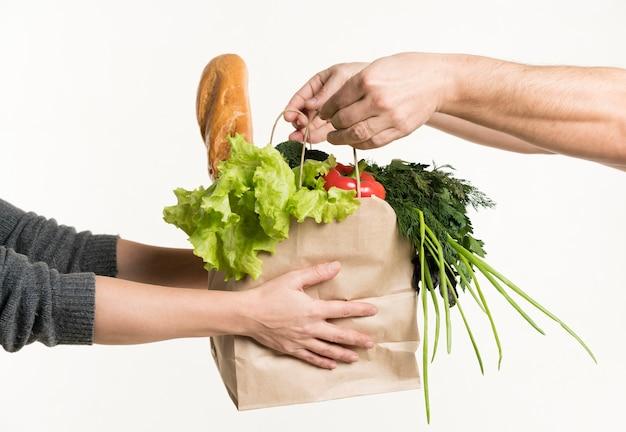 Пара рук держит пакет с продуктами Premium Фотографии