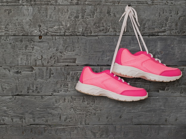 Pair pink womens running shoes hanging by the laces on the