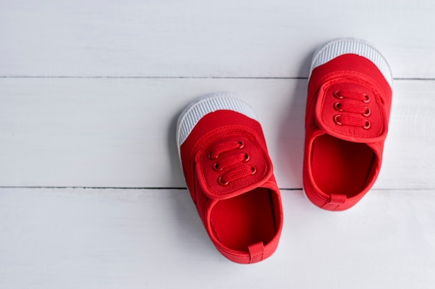 A pair of red baby boy shoes on white wooden floor Premium Photo