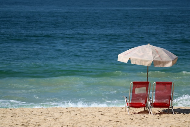 6ad23c5447 Pair of red beach chairs and pale pink parasol on the sandy beach ...