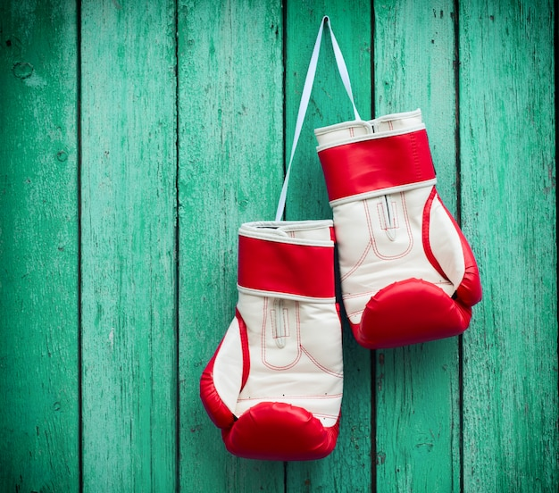 1696951046aa16 Pair of red boxing gloves hanging on a nail on a surface of green wood  surface