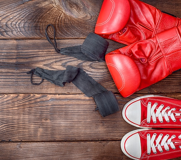 Pair of red textile sneakers and red leather boxing gloves Premium Photo