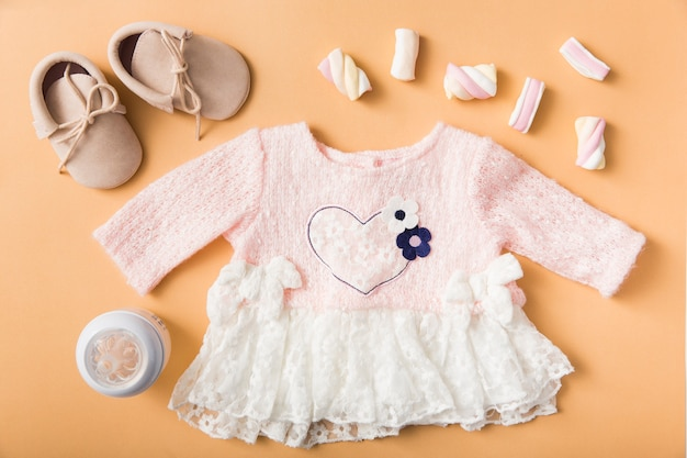 Pair of shoes; marshmallow; milk bottle and baby pink dress on an orange backdrop Free Photo