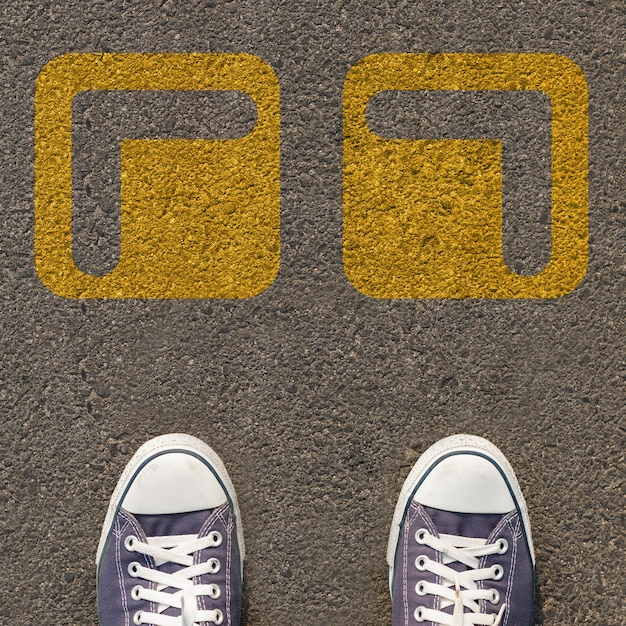 Pair of shoes standing on a road with two way yellow arrow Premium Photo