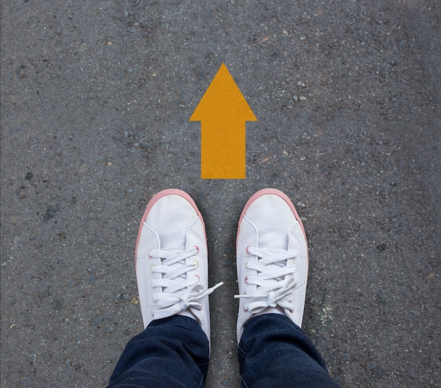 Pair of shoes standing on a tarmac road with yellow arrow ...