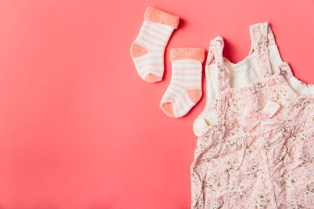 Pair of sock and baby dress on bright colored background Free Photo