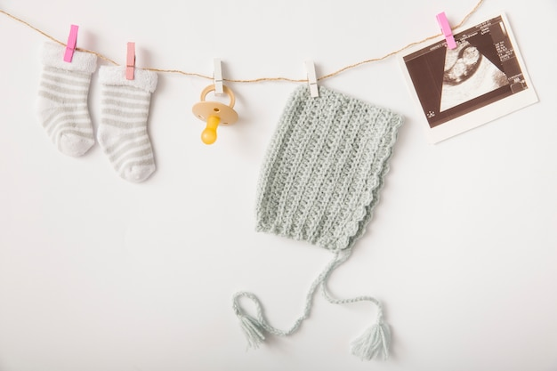Pair of socks; pacifier; headwear and sonography picture hanging on string with clothes peg Free Photo