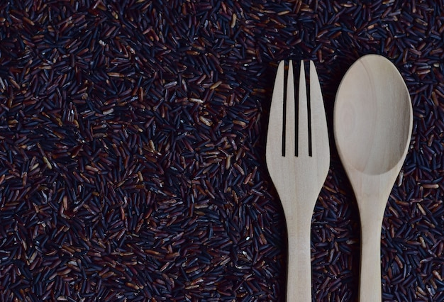 A pair of spoon and fork on riceberry (rice berry) which is a registered rice variety from Premium Photo