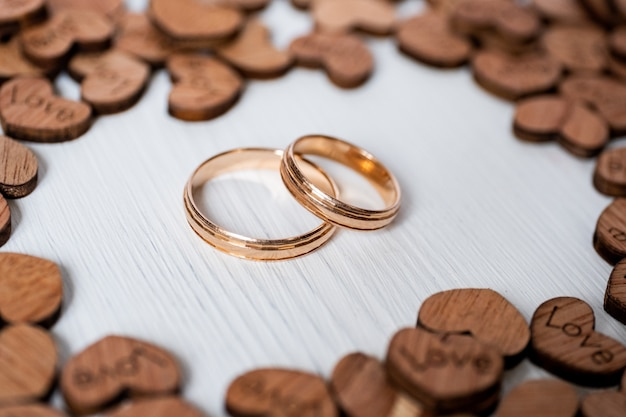 Pair wedding gold rings framed by wooden hearts on white background. side view. Premium Photo