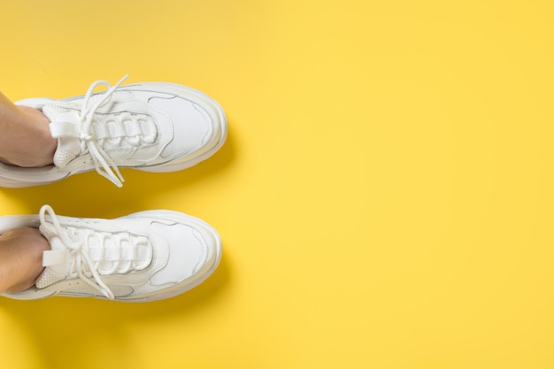 Pair of white female sneakers on yellow. flat lay, top view minimal. Premium Photo