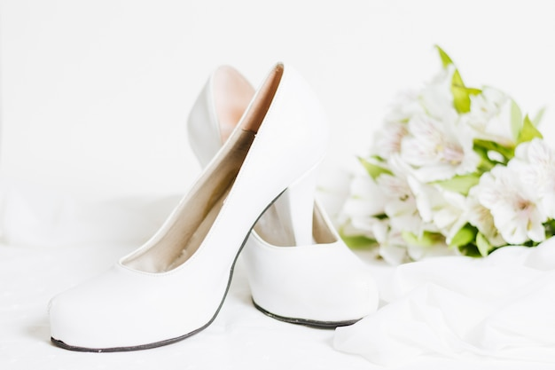 Pair of white high heels with scarf and flower bouquet on white backdrop Free Photo