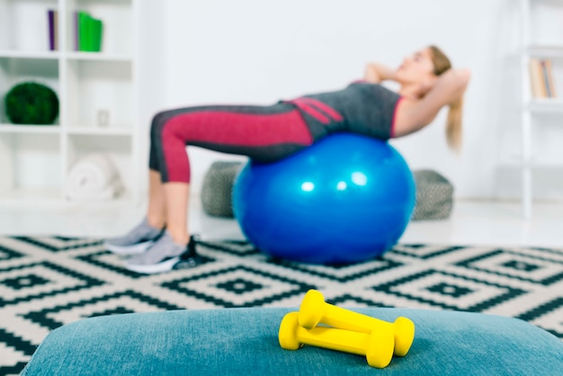 Pair of yellow dumbbells in front of woman exercising on blue pilates ball Free Photo