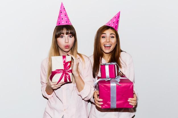 Пижамный день рождения. друзья веселятся и держат подарочные коробки. удивленное лицо, возбужденные эмоции. девочки в шляпах для вечеринок. в помещении. Бесплатные Фотографии