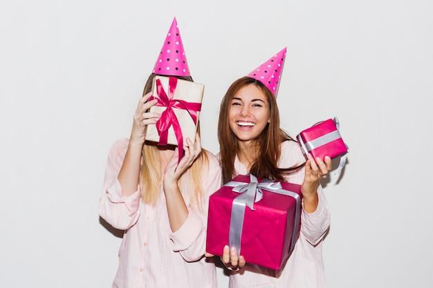 パジャマの誕生日パーティー。楽しいとギフトボックスを保持している友人。驚きの顔、出た感情。小道具パーティー帽子をかぶっている女の子。 無料写真