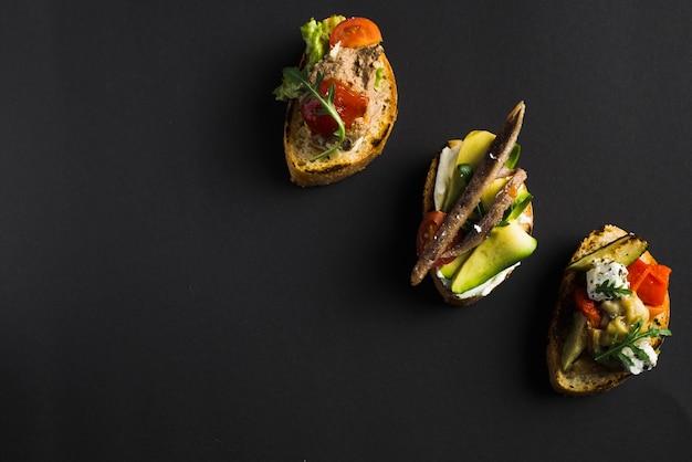 Palatable open sandwiches on black Free Photo