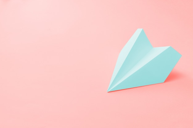 Pale blue paper plane on coral Premium Photo