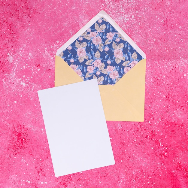 Pale colored envelope on pink marble background Free Photo