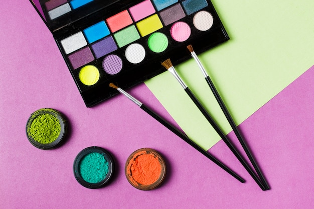 Palette of colorful eyeshadows and cosmetic brushes Free Photo