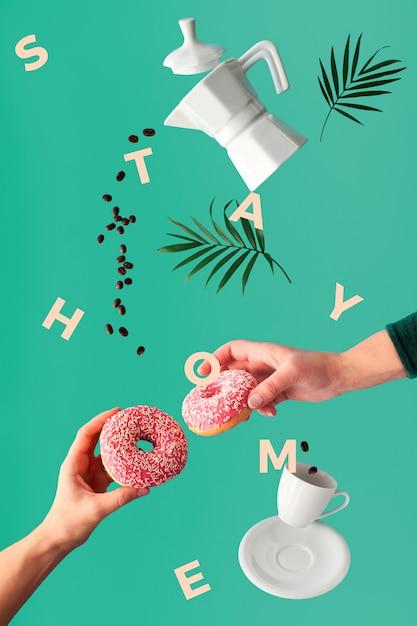 Пальмовые листья, рамка с текстом «стой домой». левитация кофе и два розовых пончика в руках. fly линия кофейных зерен. керамическая кофеварка и чашка эспрессо. Premium Фотографии