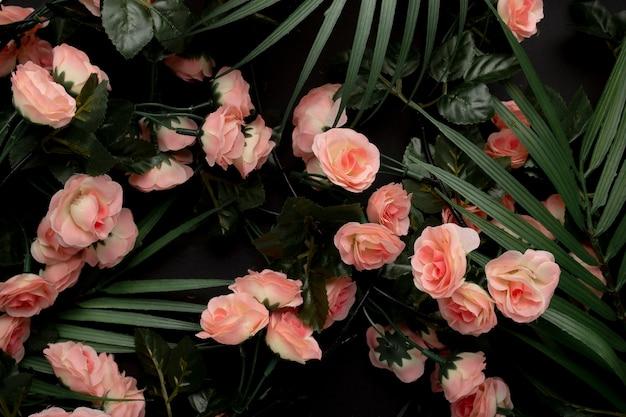 ピンクの花の背景を持つヤシの葉 無料写真