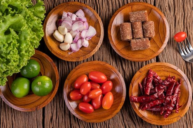Zucchero di palma, cipolle rosse, peperoni secchi, pomodori, cetrioli, fagioli lunghi e lattuga in una ciotola. Foto Gratuite