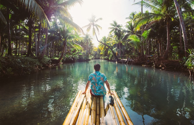 Palm tree jungle in the philippines. concept about wanderlust tropical travels. swinging on the river. people having fun Premium Photo