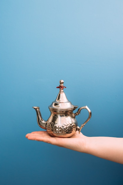 Palm of a white woman holding a metal teapot on a blue background Premium Photo